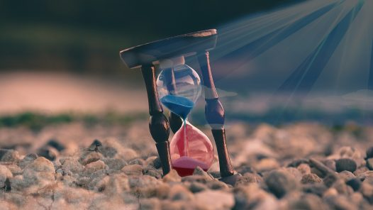 hourglass with rays of sun