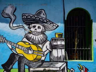 Graffiti of a skeleton with sombrero and beard playing guitar