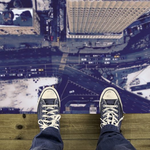 shoes on ledge high above a street
