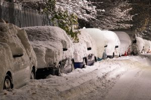 A row of snow-covered cars on a snowy street.