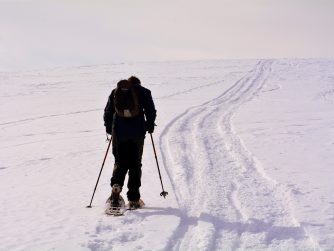 man snowshoeing up a steep snowy hill