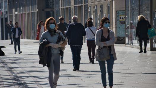 people on sidewalk with masks on