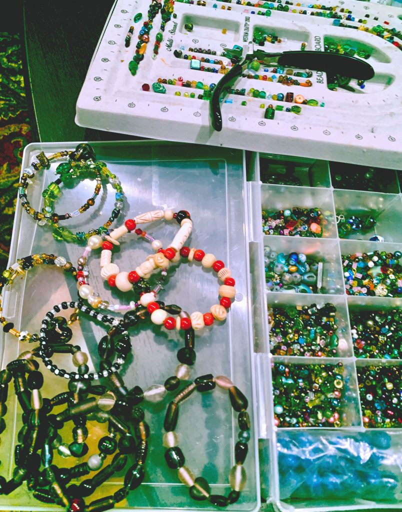 A box of beading supplies and finished beaded bracelets.  Every1dies.org
