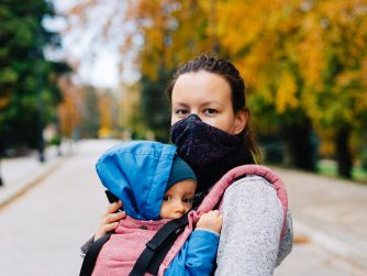 Mother wearing her mask with her baby